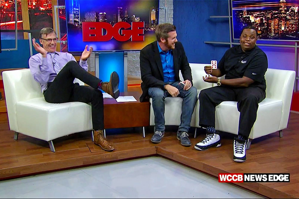 Magician Bryan Saint doing a card trick for QCB and Matt Harris on WCCB News Edge Charlotte NC