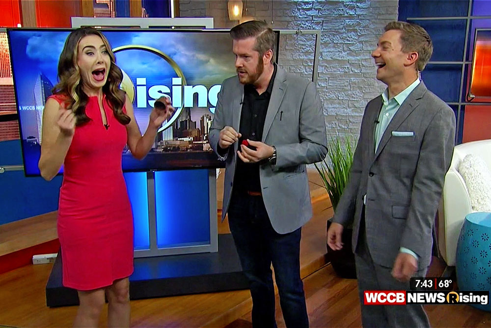 Magician Bryan Saint performing a trick with a golf ball for Julianna White and Derek James on WCCB News Rising Charlotte